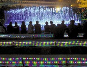 """2月24日晚,市民围坐在喷泉旁的阶梯席上欣赏""""表演""""。"""