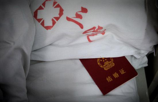 令冯莹没想到的是,在得知她的病情后不久(2013年9月23日),杨海斌便拉着冯莹去领了结婚证。图为2月28日,郑州,病床枕头下一直放着两个人的结婚证。