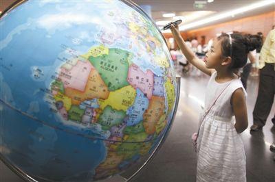 国家图书馆少年儿童图书馆,一位小女孩在玩数字地球仪