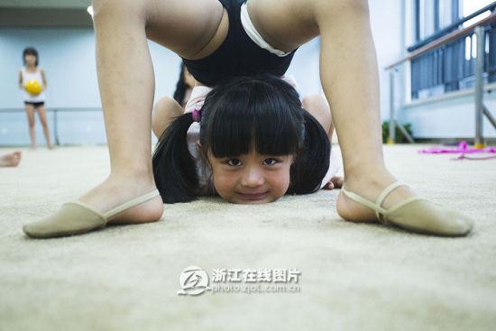 浙江在线杭州8月12日讯(浙江在线记者 童晓蕾 摄)今天下午1点半,杭州少年宫的艺术体操练习房里,15个7岁的孩子开始了今天的第二节课。假期里她们在一直在这儿接受着专业老师的授课,这个星期课程将接近尾声。 在整个课程中除了在练习动作时的认真,孩子们一直笑声连篇,欢乐充斥着课堂。也许家长们送小朋友去练习艺术体操有着不同的原由,塑造体形、提升气质、强身健体,或是有朝一日走上冠军的领奖台。可孩子们并没有那么多的想法,她们只是很快乐,很享受上课的过程,就算她们需要将身体折到常人无法到达的程度,会感到疼痛,却还