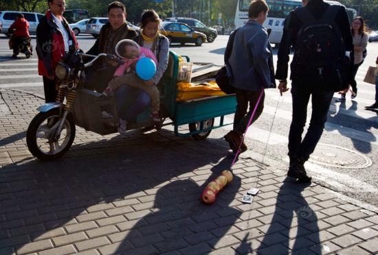 """行为艺术家在北京街头""""遛苹果""""引围观"""