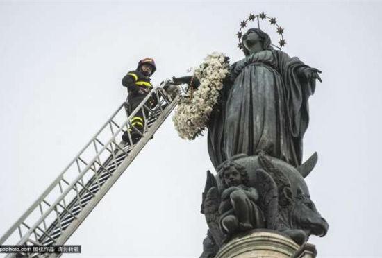 """罗马圣母雕像换""""新装""""消防员送花环"""