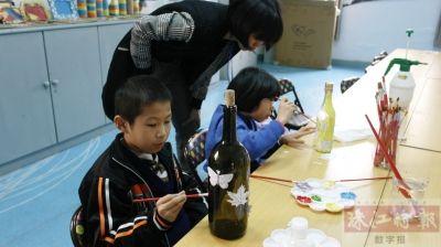 课堂上,孩子们为玻璃瓶涂上心仪的颜料制作小花瓶.图片