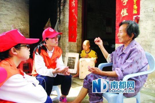 何婆婆和志愿者聊天,远处坐着的是她的儿子阿章。通讯员供图