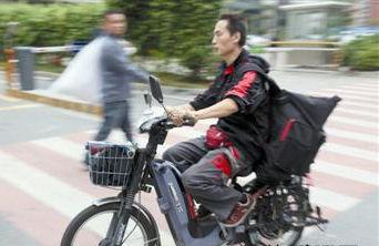 南城三元路,一名快递员正忙着送快递。