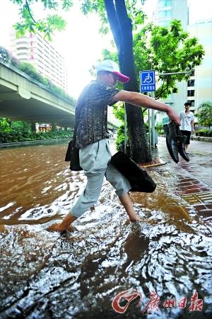 一位路人提着鞋子过街。记者莫伟浓 摄