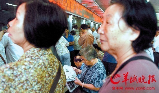 看病难、看病贵,连挂号都要早晨5 点排队,这位阿婆搬来小凳子坐着看报纸等候羊城晚报记者林桂炎摄(资料图片)