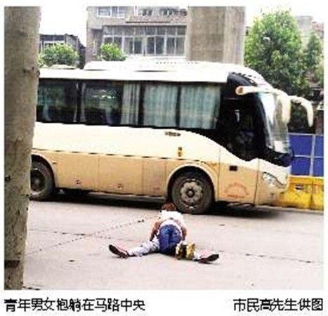 青年男女抱躺马路中央