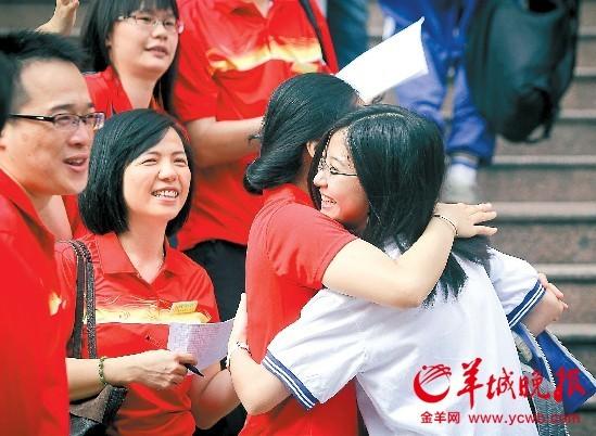 """昨天上午,广州市第十六中学考场门口,送考老师全体以""""红衫军""""亮相,为考生助威 羊城晚报记者何奔摄"""