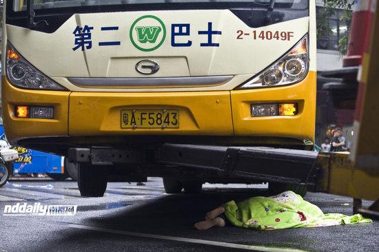 6月12日上午10时40分许,现场工作人员将事发的公交车撬起,用毯子将阿婆的尸体盖住。 实习生 黎湛均 南都记者 张志韬 摄
