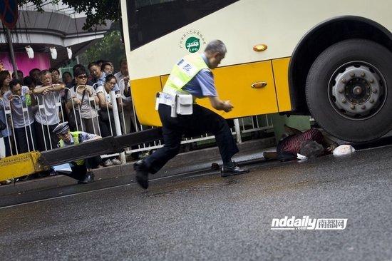 现场工作人员将事发的公交车撬起,交警连忙上前调查取证。