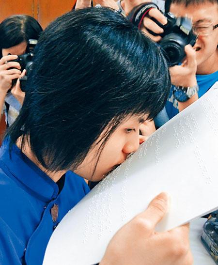 曾芷君15日即场示范阅读点字,把笔记放在双唇前,逐字逐句细读内容,骤眼似是亲吻纸张。香港星岛日报图