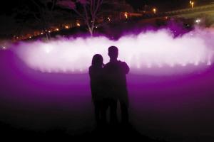 2月24日晚,一对情侣相依在音乐喷泉旁入神观赏。