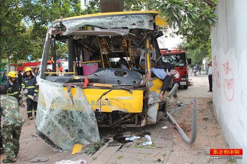 """深圳朗山""""极速""""公交车撞泥头车,13人受伤。涉事的公交车车头被撞损毁严重,工作人员在处理现场。"""