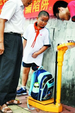 一名小男生把书包放在秤上