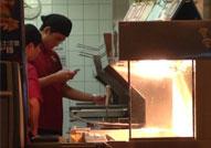 麦当劳员工炸薯条玩手机